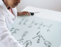 diligent african american scientist developing solution to chemical problems in light office