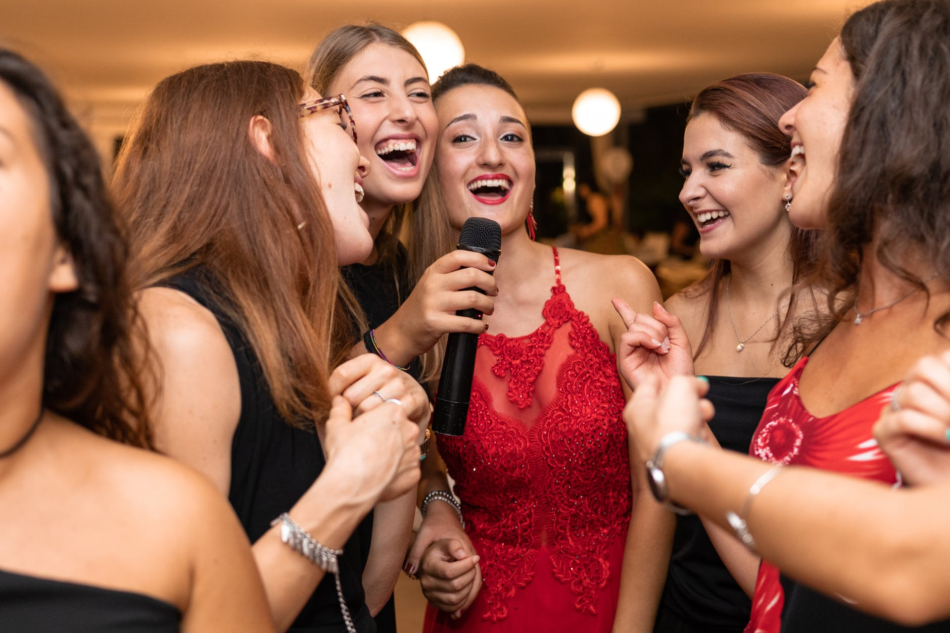 elegant ethnic women with microphone congratulating friend while laughing