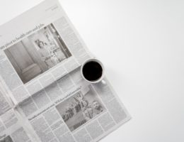 white ceramic mug on top of a newspaper