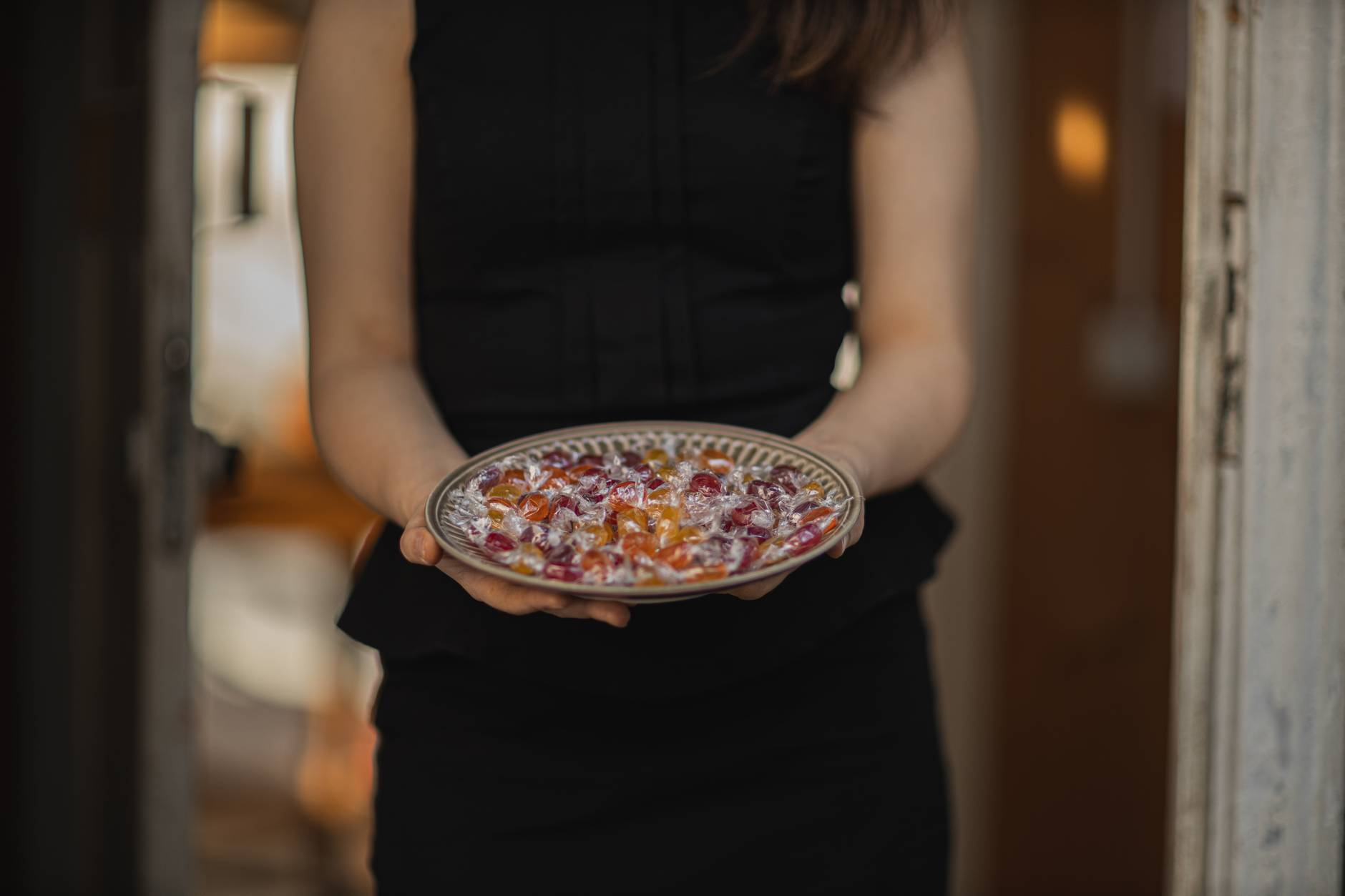 woman in black tank top holding plate with candies