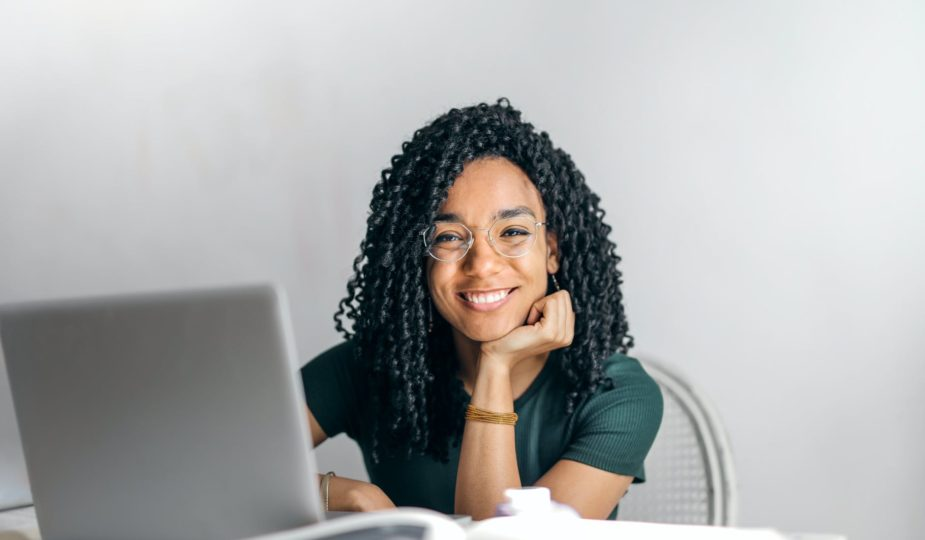 happy ethnic woman sitting at table with laptop