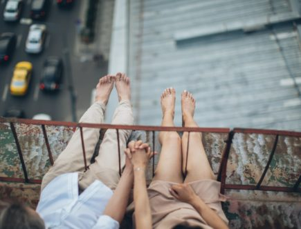crop couple resting on rooftop on height