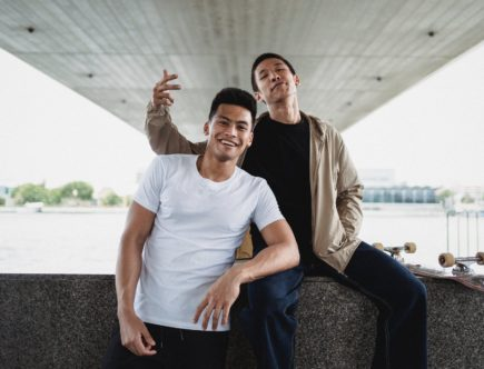 positive young male friend leaning on knee of friend on river embankment in city