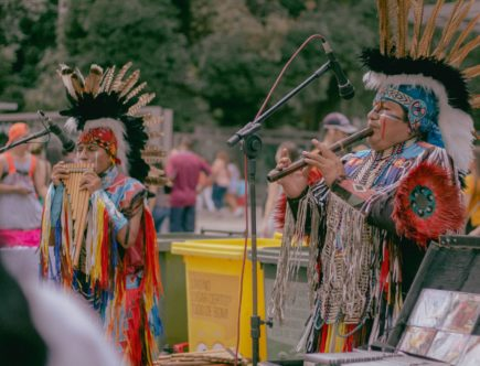 photo of two native americans playing woodwind instruments
