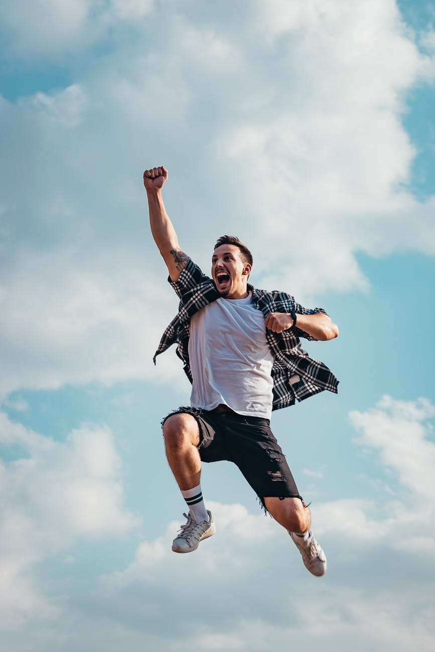 low angle photography of man jumping