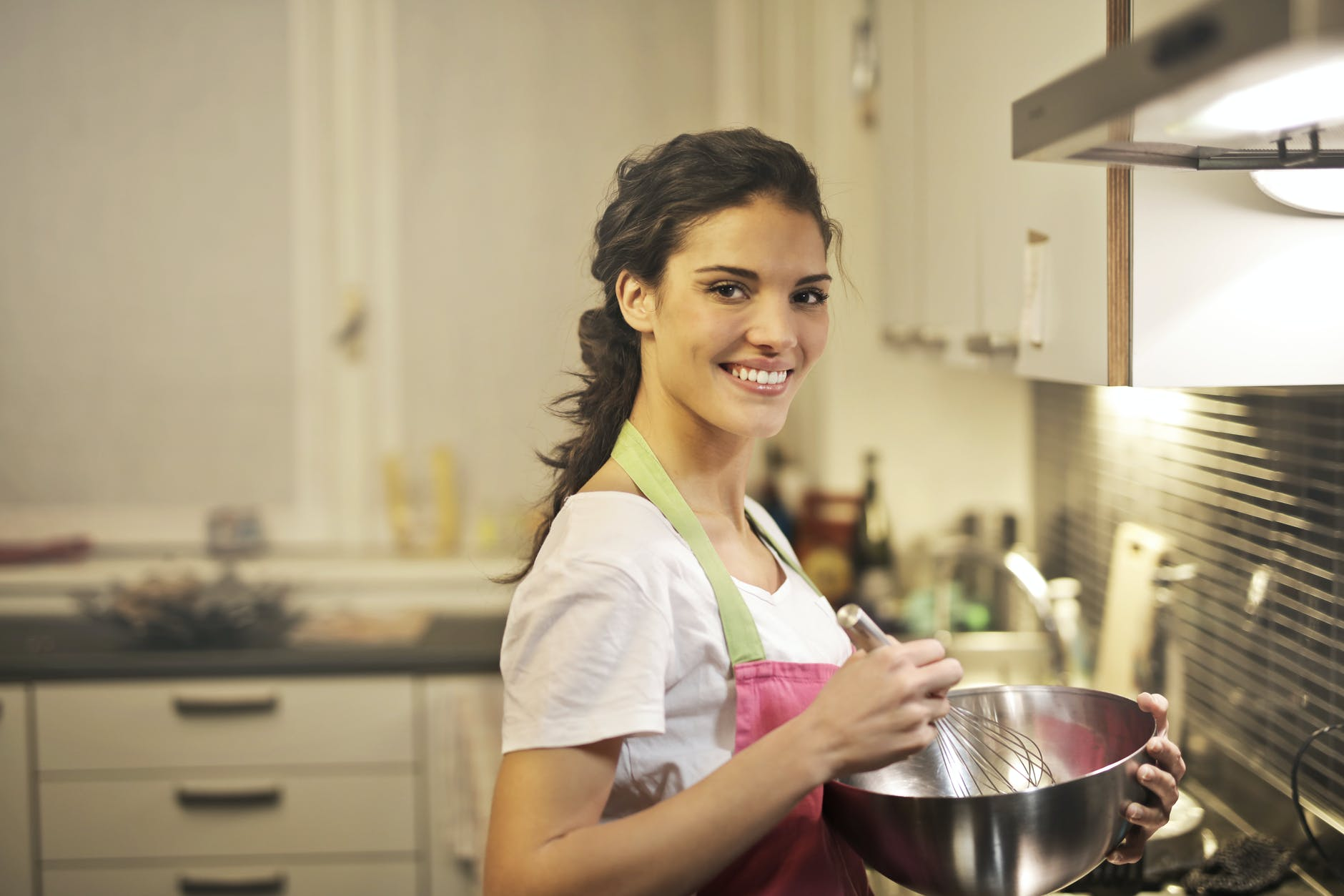 delighted ethnic woman cooking in kitchen