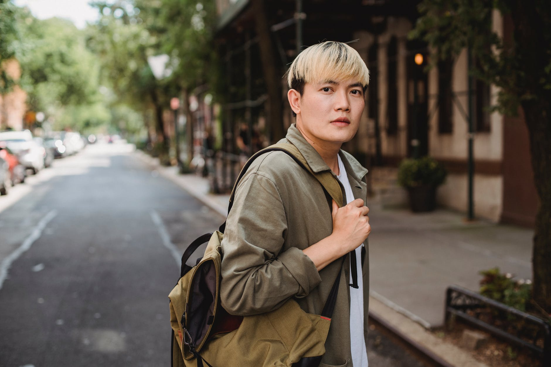 calm asian man with backpack standing on sunny sidewalk