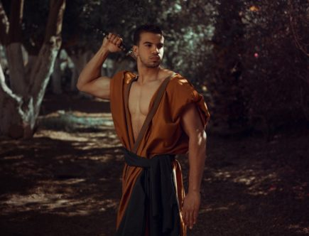man wearing orange traditional costume holding sword while standing surrounded with green trees