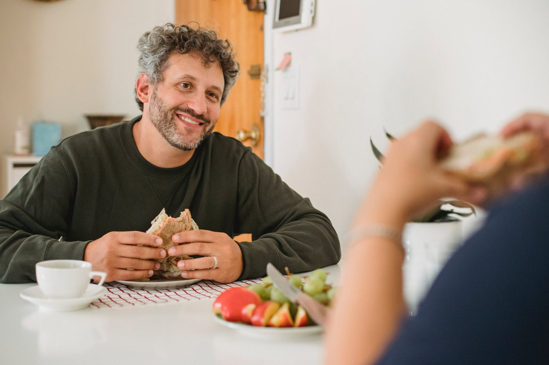 cheerful bearded man having breakfast with wife