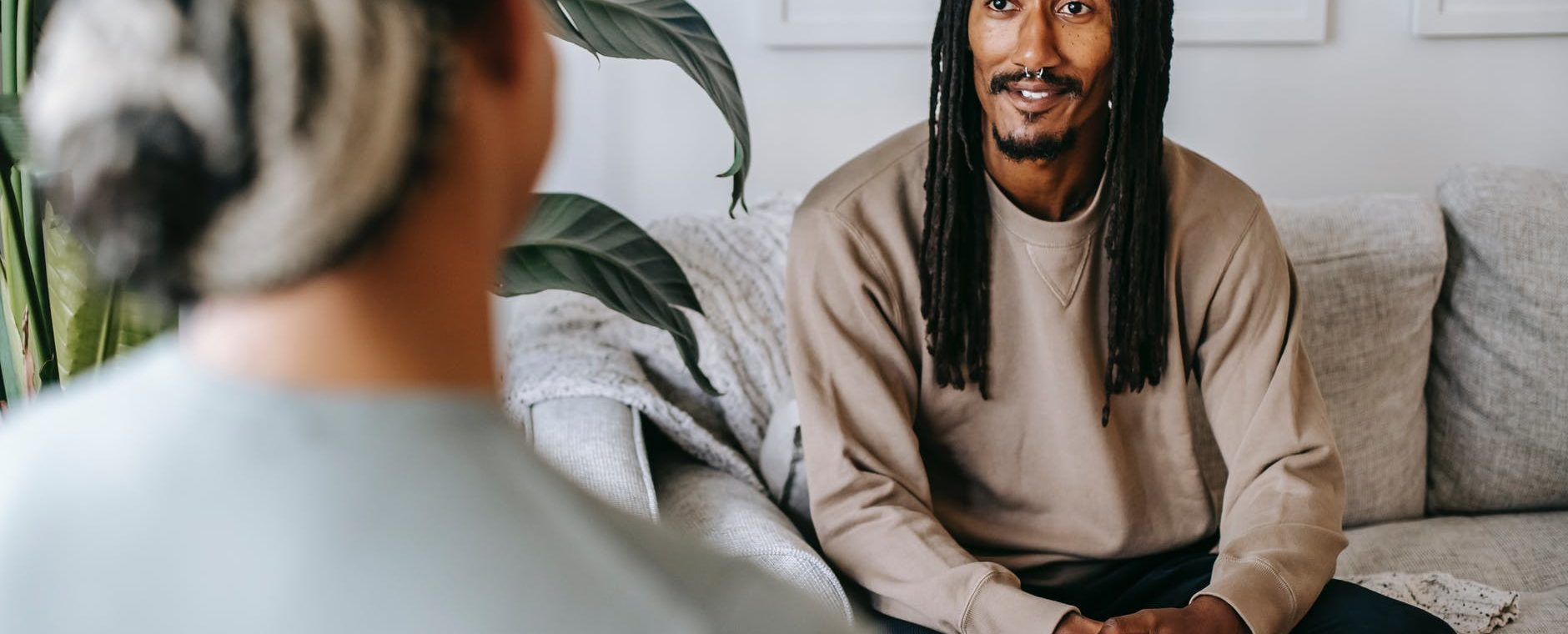 black man talking to unrecognizable girlfriend in living room