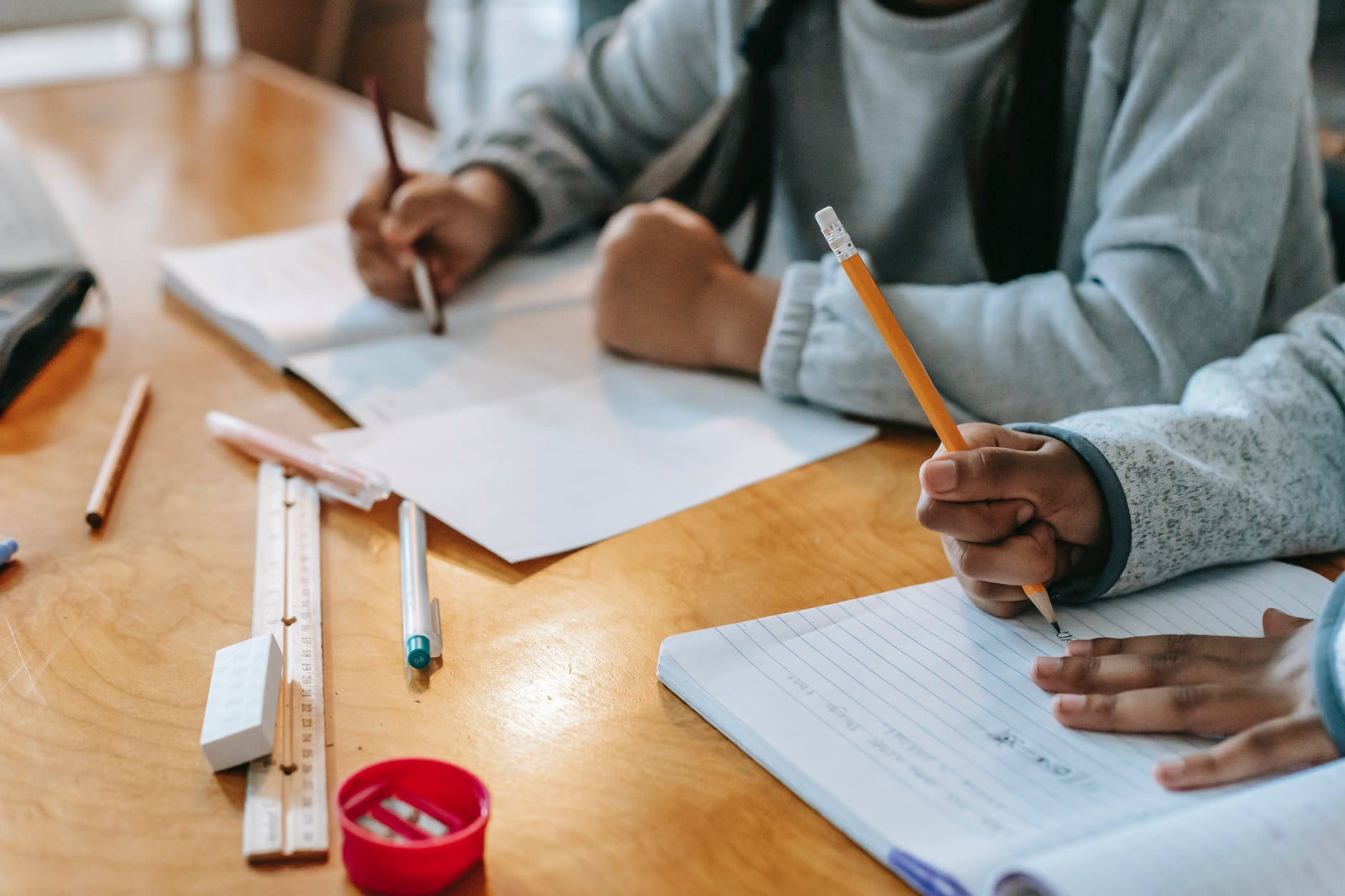 crop pupils writing in copybook on desk